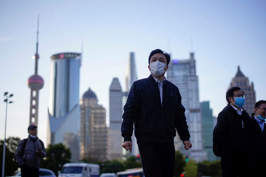 People wear protective face masks at Lujiazui financial district in Shanghai, China, on March 19, 2020.
