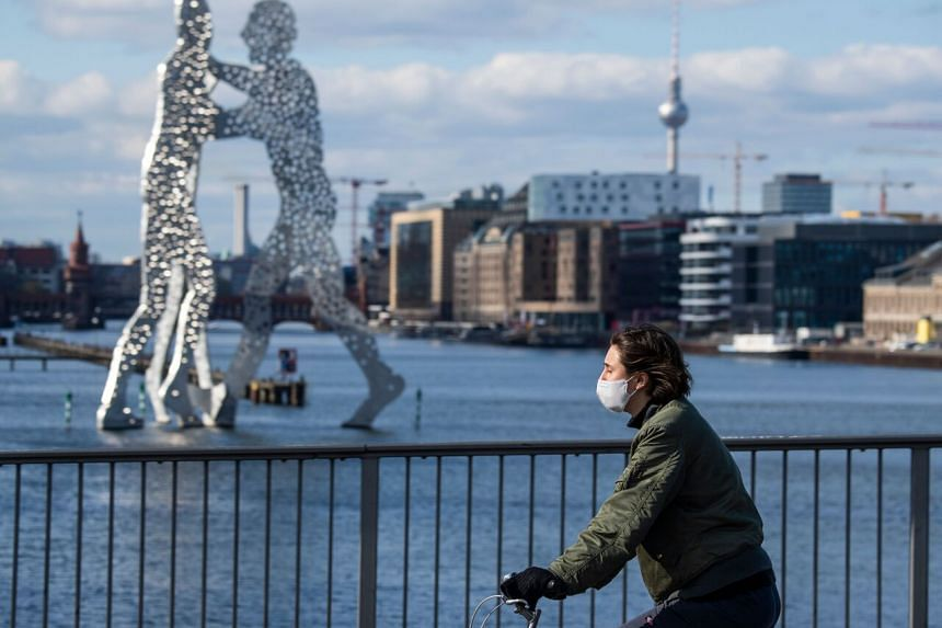 A woman wearing a surgical mask cycles over the river Spree in Germany on March 21, 2020.