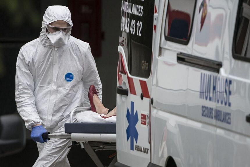 A medical worker wearing a protective suit unloads a woman from an ambulance on a stretcher at the Emile Muller Hospital in Mulhouse, France, on March 22, 2020.