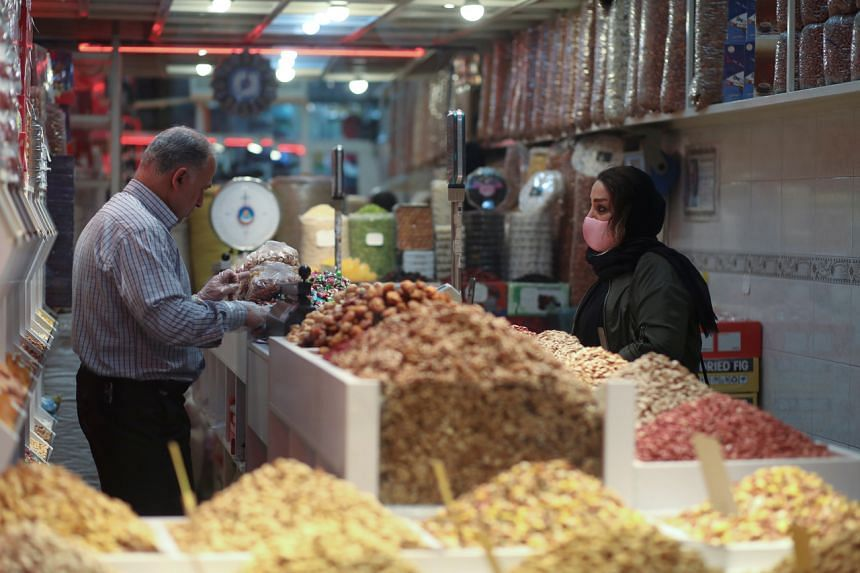 An Iranian woman wears a protective face mask as she buys nuts at Tajrish Bazar, in Teheran, Iran, on March 18, 2020.
