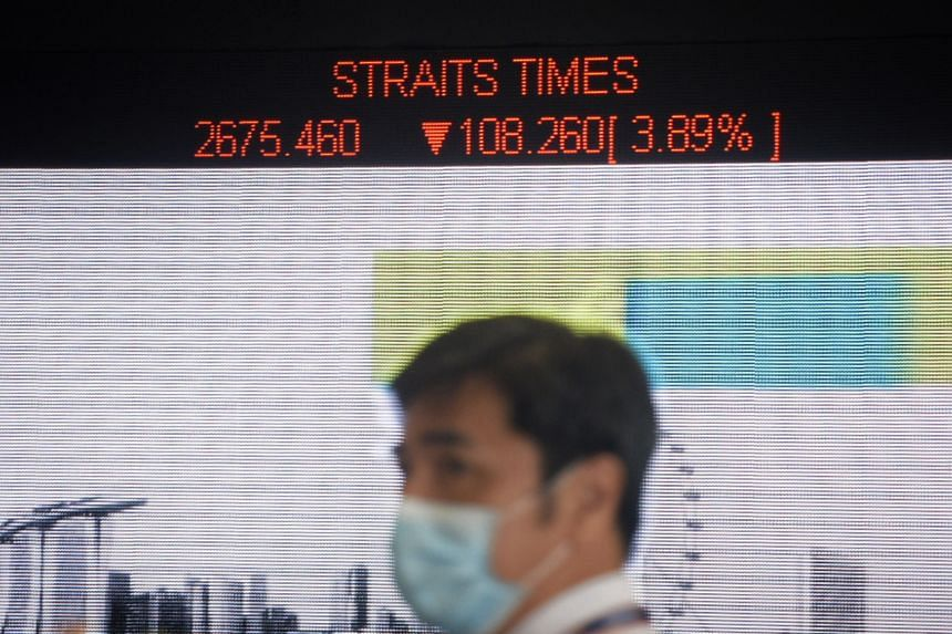 A security guard donning a mask is seen in front of an electronic stock board showing the Straits Times Index at The SGX Centre on March 12, 2020.