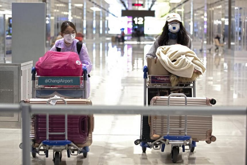 Travelers at the arrival hall of Changi Airport Terminal One in Singapore, on March 19, 2020.