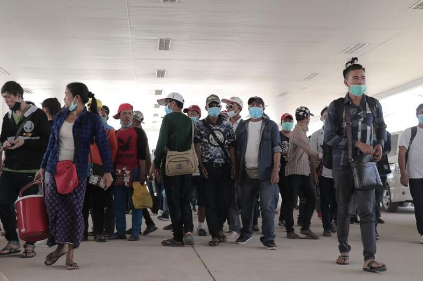 Myanmar nationals with masks at the immigration post in Myawaddy near the Thai border, on March 23, 2020.