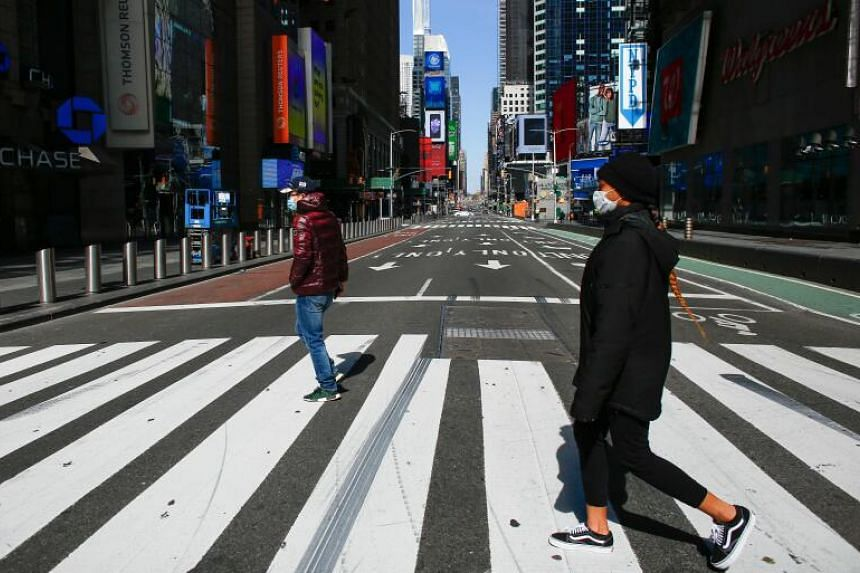 People wear face masks as they cross a street in Times Square, New York City, on March 22, 2020.