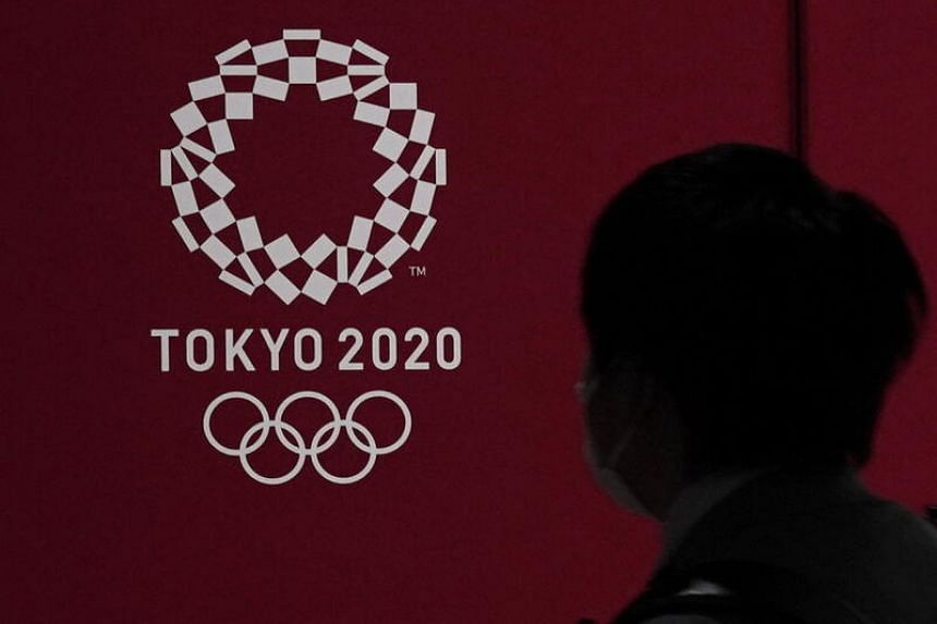 A pedestrian with a mask looks at the emblem of the Tokyo Olympic Games in Tokyo, on March 23, 2020.