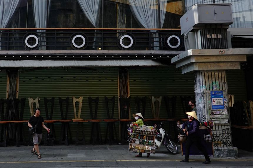 In a photo taken on March 16, 2020, people walk past a closed bar in the tourist area of Bui Vien due to the coronavirus outbreak in Ho Chi Minh city, Vietnam.