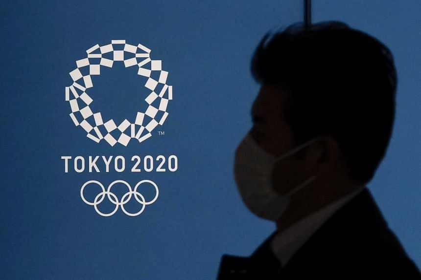 A pedestrian wearing a mask walks past the emblem of the Tokyo Olympic Games in Tokyo, Japan, on March 23, 2020.