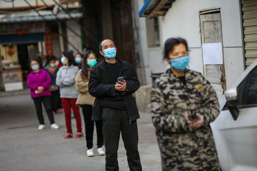 A photo taken on March 18, 2020, shows residents lining up to pick up pork which was delivered to their quarantined compound in Wuhan.