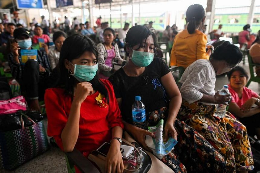 People wear face masks as a preventive measure against the Covid-19 coronavirus while waiting for a ride at the central railway station in Yangon, Myanmar, on March 19, 2020.