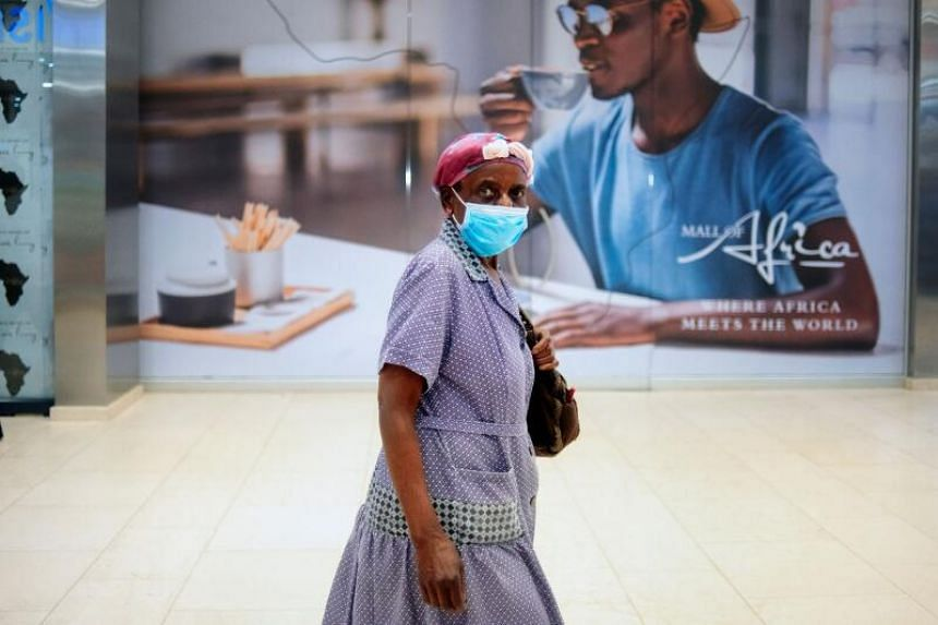 A woman wears a mask amid concerns over the spread of the Covid-19 coronavirus while she walks along a corridor of the Africa Mall in Johannesburg, on March 20, 2020.