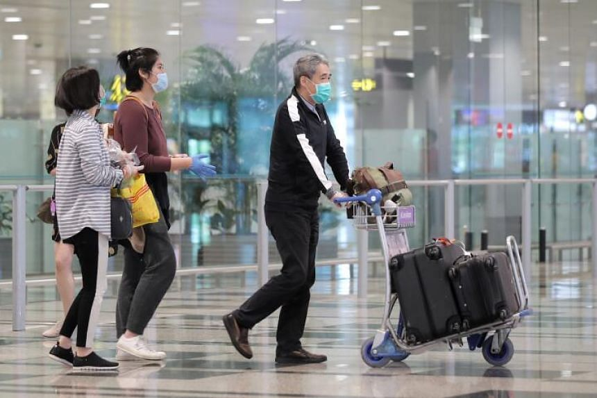 A passenger (centre) is immediately given a pair of latex gloves to wear upon arrival at Changi Airport Terminal 3 on March 24, 2020.