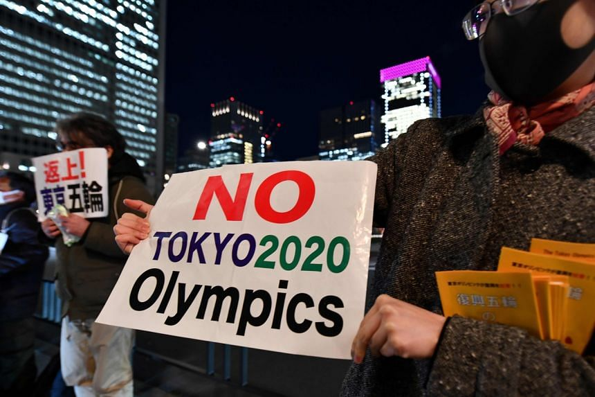 Protesters opposed to the Tokyo 2020 Olympics in front of a railway station in Tokyo on March 24, 2020.