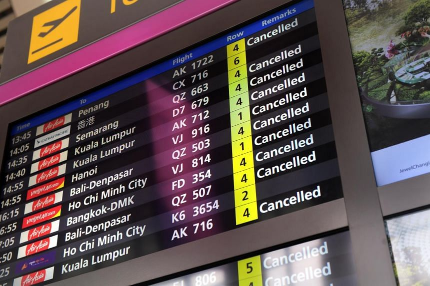 In a photo from March 20, 2020, a flight information display system at Changi Airport Terminal 4 shows a list of cancelled flights.