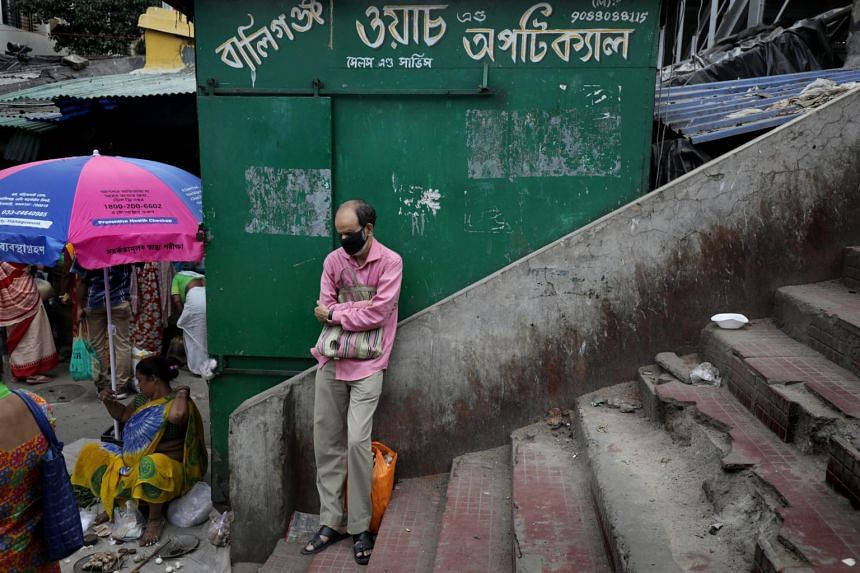 An Indian commuter wears a protective face mask as he waits with a full ration bag in Kolkata, India, on March 23, 2020.