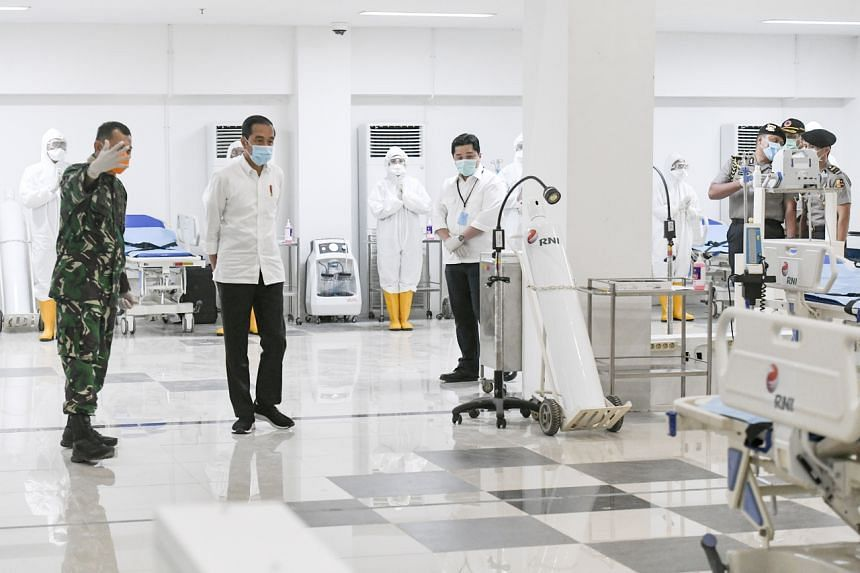 Indonesian President Joko Widodo (second from left) inspects a room during a visit to the Asian Games athlete's village which has been converted into a temporary hospital for Covid-19 patients in Jakarta on March 23, 2020.