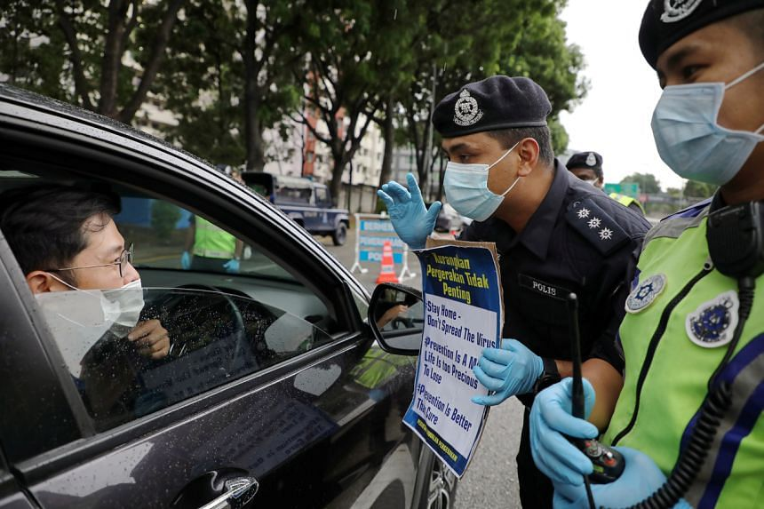 Police officers wearing protective masks show a placard to a driver at a roadblock set up to enforce movement control order in Kuala Lumpur, Malaysia, on March 23, 2020.