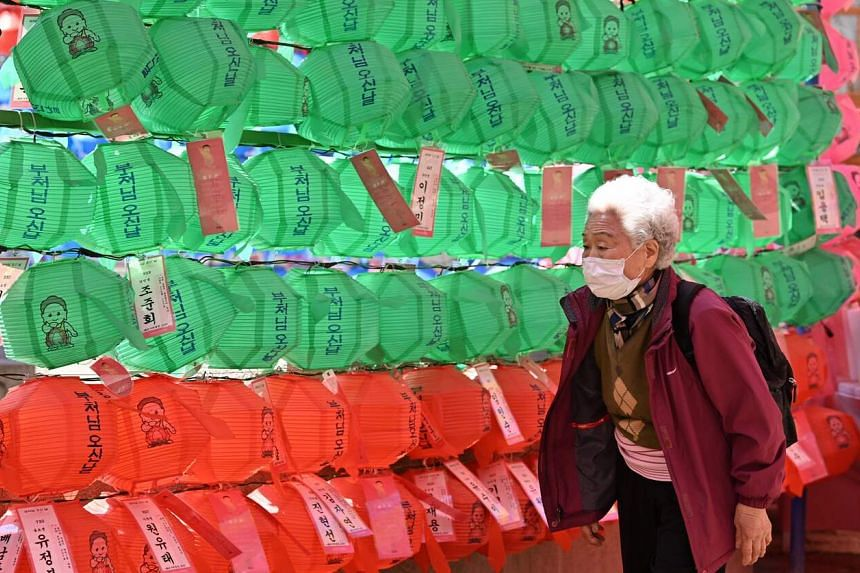 An elderly woman wearing a face mask walks past lotus lanterns ahead of Buddha's birthday at Jogyesa Temple in Seoul, South Korea, on March 23, 2020.