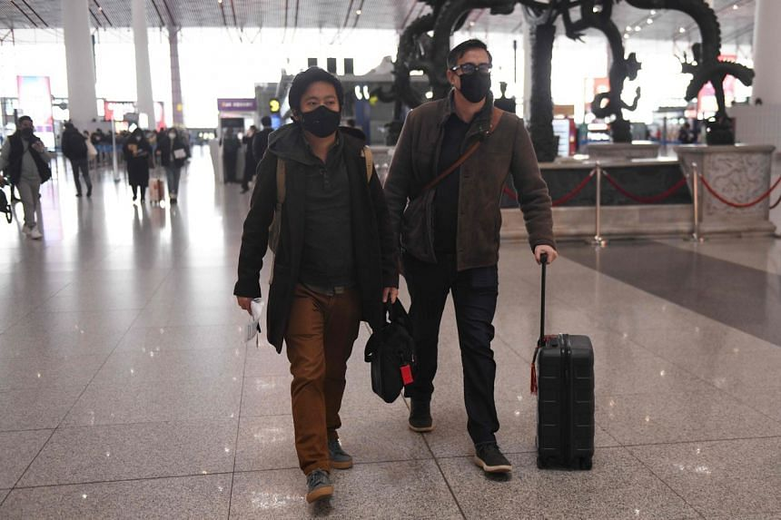 A photo from Feb 23, 2020, shows Wall Street Journal reporters Philip Wen (left) and Josh Chin at Beijing Capital International Airport after they were ordered to leave the country.