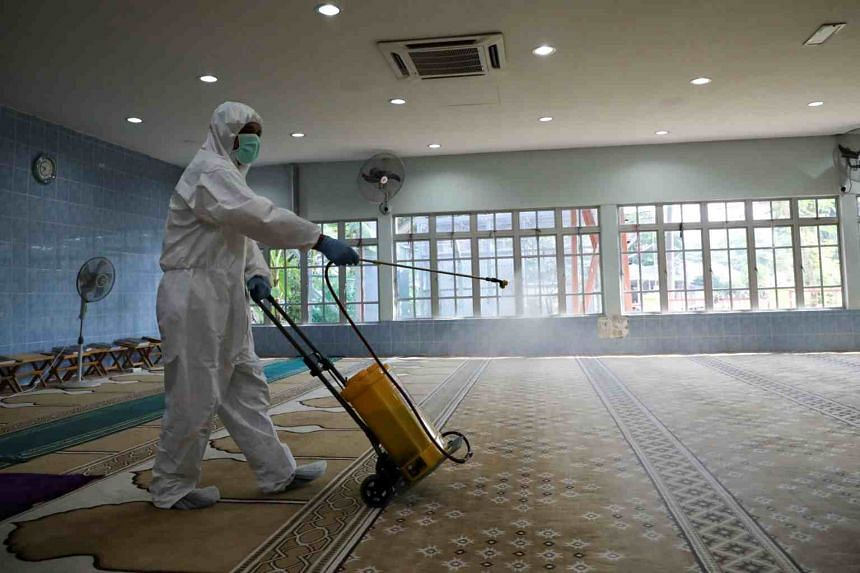A worker spraying disinfectant at a mosque, which is closed during the movement control order due to the outbreak of the Covid-19 coronavirus, in Kuala Lumpur, Malaysia, on March 24, 2020.