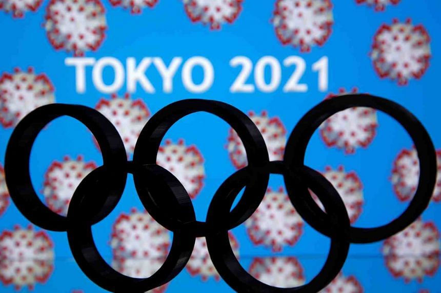 """A 3D printed Olympics logo is seen in front of displayed """"Tokyo 2021"""" words in this illustration taken on March 24, 2020."""