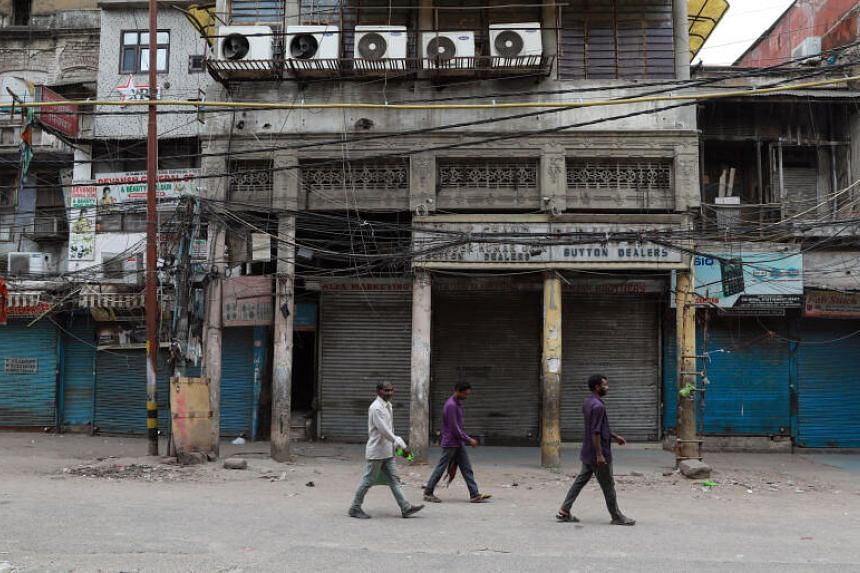 People walking past closed shops in a nearly deserted wholesale market during lockdown in the old quarters of New Delhi, on March 24, 2020.