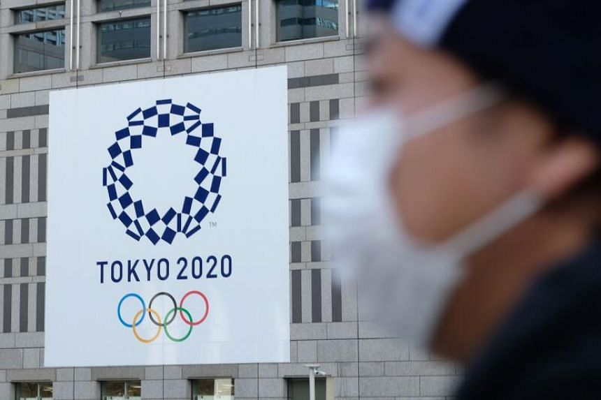 In this file photo taken on March 19, 2020, a man wearing a mask passes the logo of the Tokyo 2020 Olympic Games displayed on the Tokyo Metropolitan Government building.