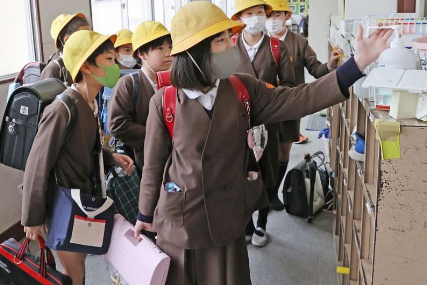 In a photo taken on Feb 28, 2020, elementary school children disinfect their hands before leaving school in Osaka, Japan.