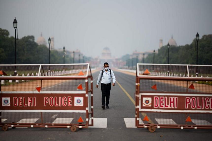 A man walks on a deserted Rajpath leading to the Presidential Palace during a government-imposed lockdown in New Delhi, on March 24, 2020.