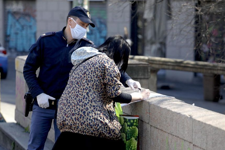 Italian law enforcement officers carry out checks to verify that there are valid reasons for the movement of Milanese residents, March 24, 2020.