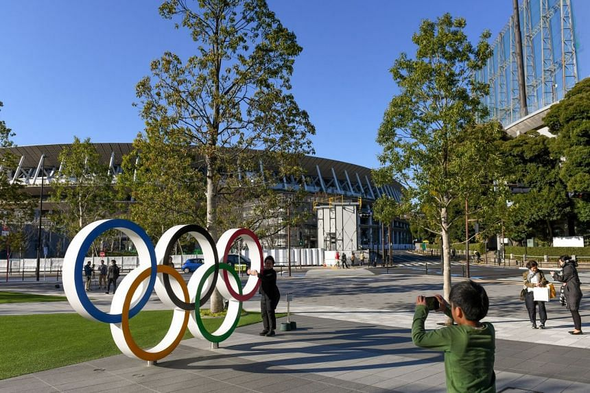 Pedestrians take photos of the Olympics rings at the Japan Olympic Museum in Tokyo, March 24, 2020.
