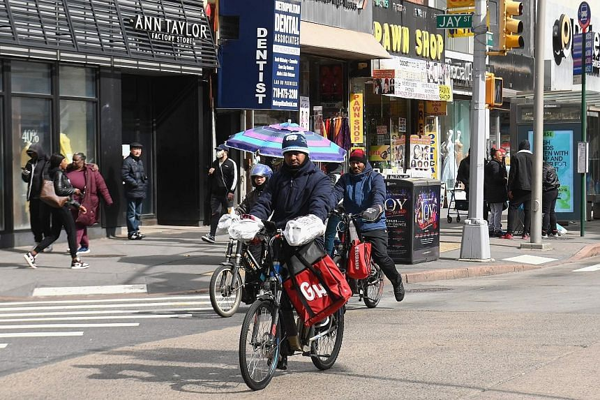 Food delivery riders in Brooklyn, New York. Many riders and drivers wear gloves and masks, and regularly apply disinfectant gel. Some wrap plastic around the handlebars of their bicycles.
