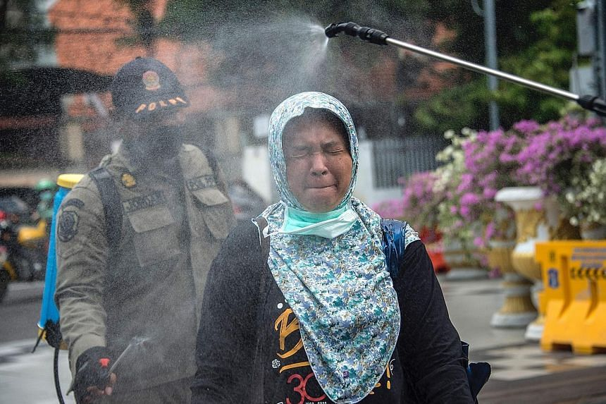 A woman being sprayed with disinfectant before entering a local government office in Surabaya, Indonesia, on Monday. The country now has a total of 686 recorded infections.
