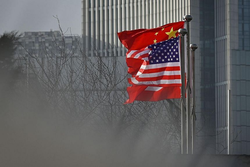 Chinese and US national flags outside an office building in Beijing. Last week, China announced that all American journalists at three US papers based in the country whose credentials were set to expire this year had to hand in their press cards with