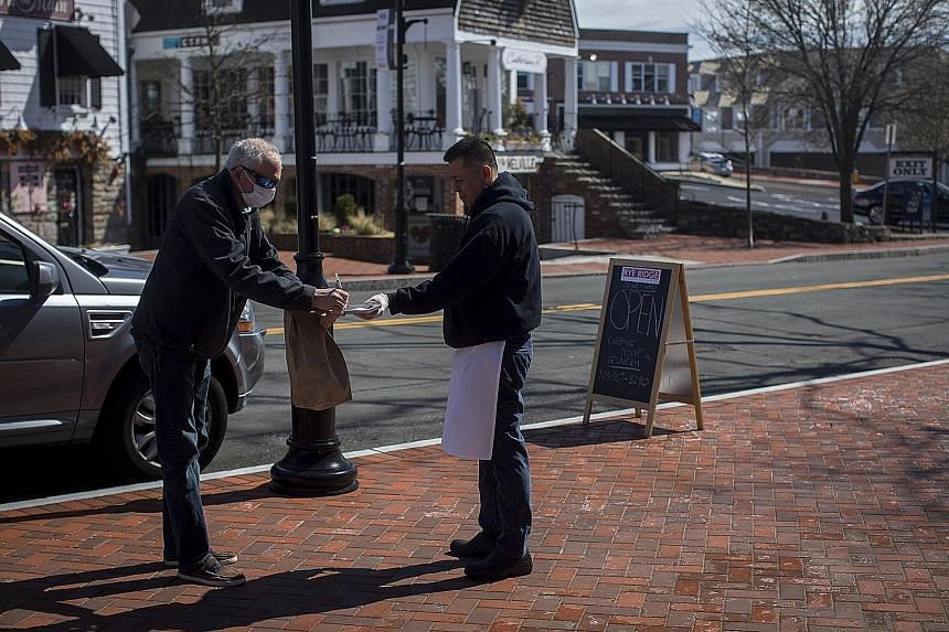 Mr Mitch Palais, 59, picking up a takeaway order from Rye Ridge Deli in Westport, in the US state of Connecticut, on Sunday. Mr Palais was tested for Covid-19 but, as of Sunday, had yet to receive results. Westport, a town of 28,000 in Fairfield Coun