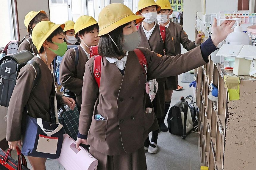 Japanese elementary schoolchildren at an Osaka school disinfecting their hands last month. Most schools in Japan are set to reopen on April 6, after a month-long closure to keep the virus spread in check. PHOTO: AGENCE FRANCE-PRESSE