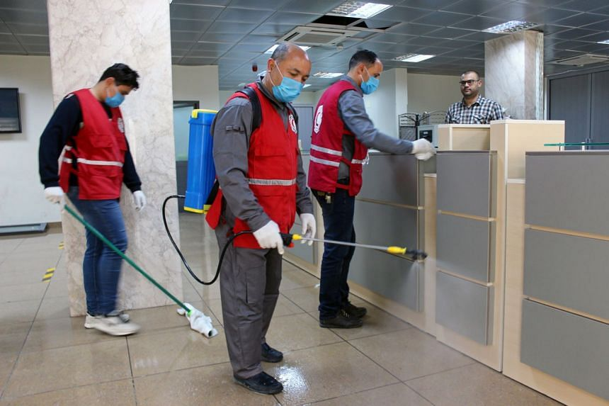 Members of Red Crescent spray disinfectant, as part of precautionary measures against the coronavirus at government offices in Misrata, Libya, on March 21, 2020.