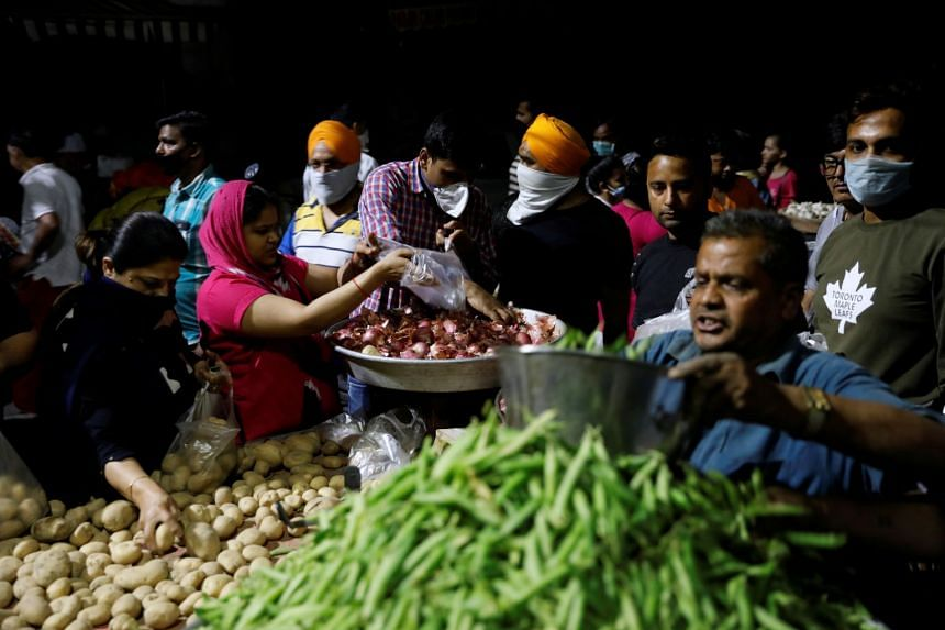 People buy vegetables at a market after India's Prime Minister Narendra Modi called for a nationwide lockdown starting midnight, in New Delhi, on March 24, 2020.