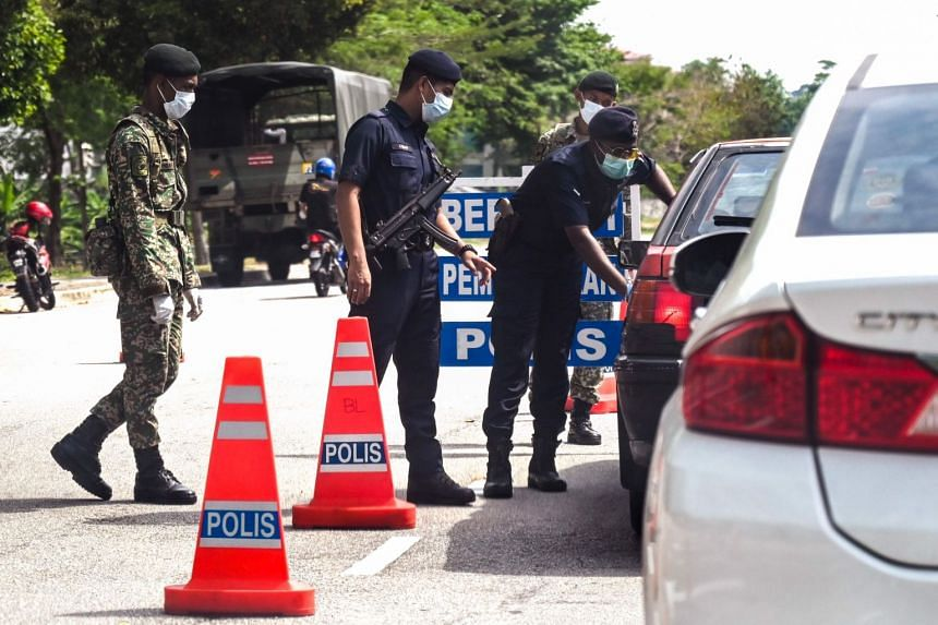 Malaysian soldiers and police officers at a Penang roadblock during the partial lockdown in Malaysia on March 24, 2020.