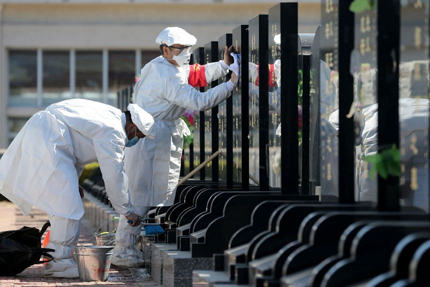 Staff members wearing protective suits and face masks sweep tombs on behalf of the families by request ahead of the Chinese Qingming Festival at the Babaoshan Revolutionary Cemetery in Beijing on March 23, 2020.