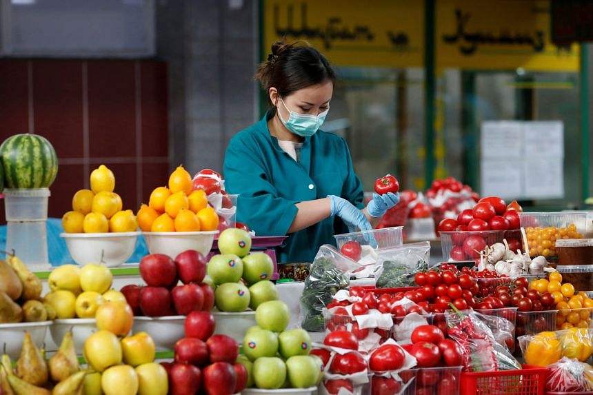 A vendor wearing a protective face mask packs vegetables at a local food market in Almaty, Kazakhstan, on March 20, 2020.