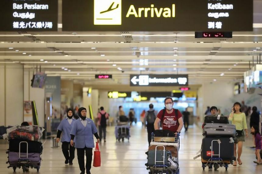 Fewer travellers are seen at Changi Airport Terminal 2 on March 24. The Government's key objective in fighting the virus is also to focus resources on the large number of Singaporeans returning from overseas, National Development Minister Lawrence Wo