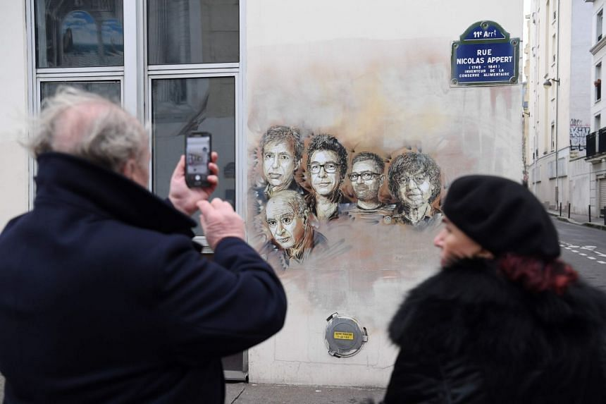 In a 2018 picture, a man photographs a portrait of late Charlie Hebdo staff (from left) Bernard Maris, Georges Wolinski and Bernard Verlhac (aka Tignous), Stephane Charbonnier (aka Charb) and Jean Cabut (aka Cabu) near the magazine's offices.