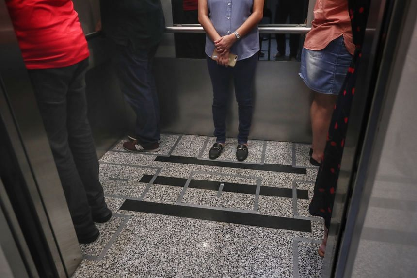 Office workers practising social distancing in the lift at Maybank Tower, on March 20, 2020.