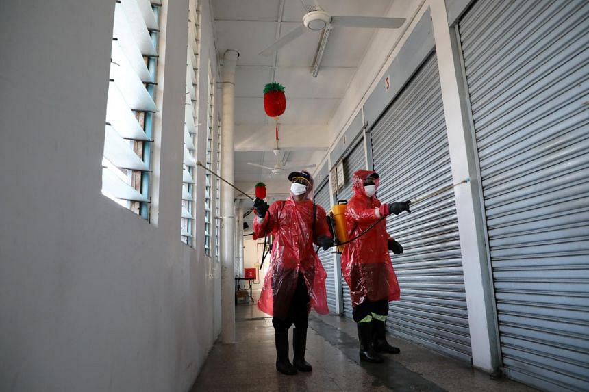 Workers spray disinfectant at a market, which is closed during the movement control order in Kuala Lumpur on March 24, 2020.