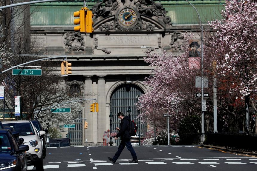 A man wearing a protective mask walks alone across a nearly empty Park Avenue near Grand Central Terminal in Manhattan, New York City, on March 24, 2020.
