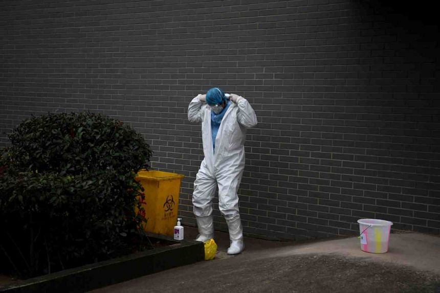 A medical worker takes off his protective gear in China's Yunan province on Feb 9, 2020.