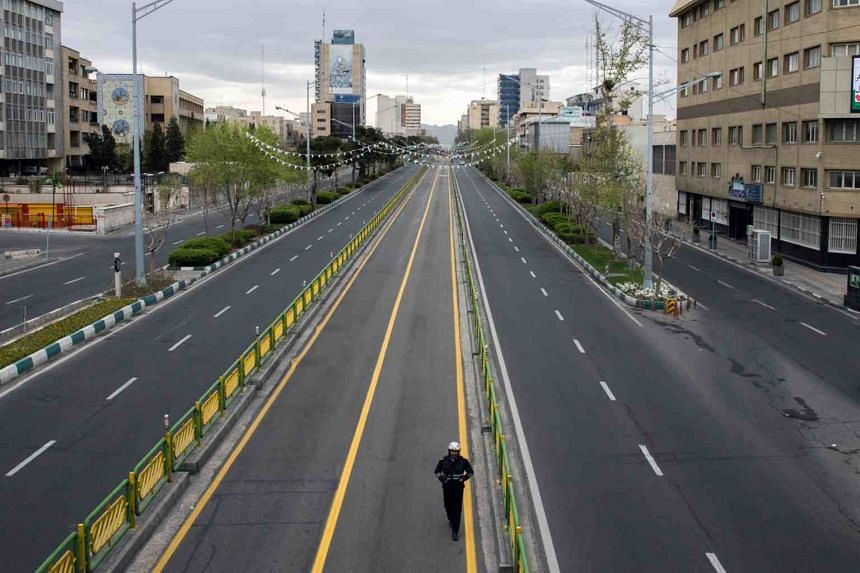 An officer patrols a road in Teheran devoid of traffic due to the coronavirus pandemic, on March 22, 2020.