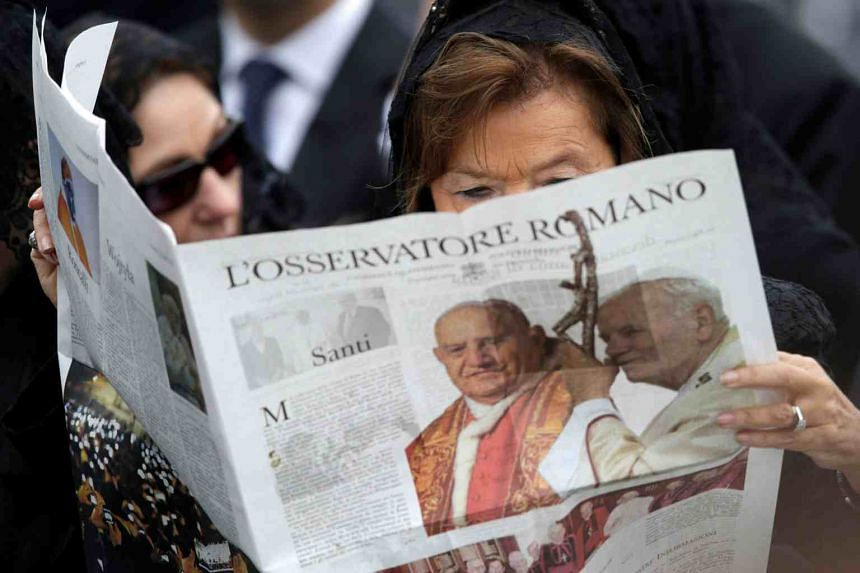 In a file photo taken on April 27, 2014, a woman reads a copy of the Vatican newspaper L'Osservatore Romano as she waits for the canonisation ceremony in St Peter's Square at the Vatican.