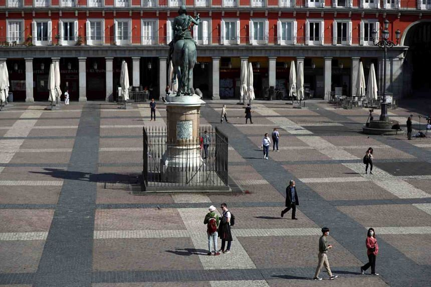 People with protective face masks walk through Plaza Mayor Square in central Madrid, Spain, on March 13, 2020.