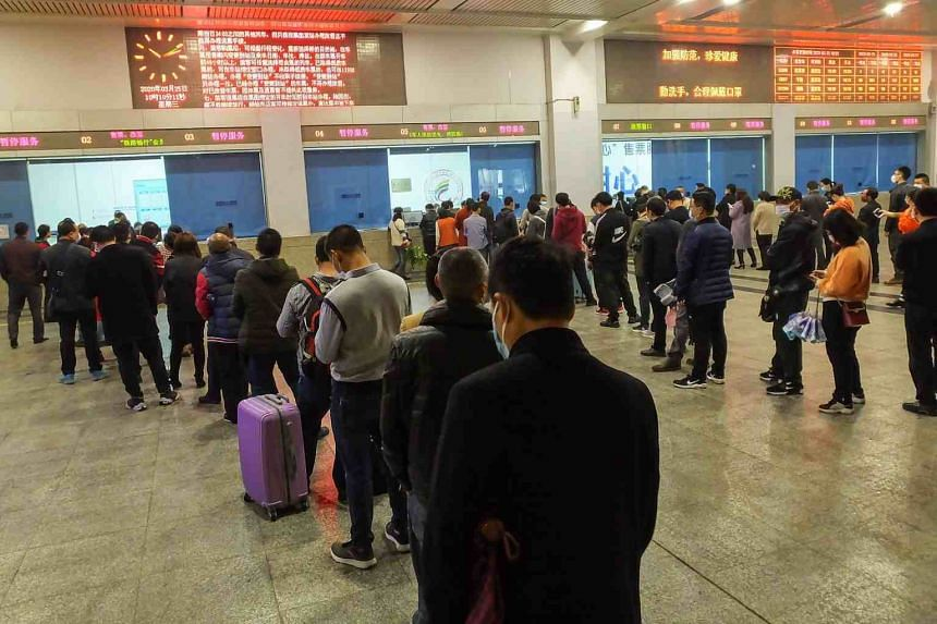 People queue to buy train tickets at Yichang East Railway Station in Yichang in China's central Hubei province, on March 25, 2020.